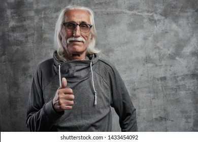 Modern gray-haired caucasian old man with a mustache shows thumb up and smiles, joyful happy face against gray wall in studio