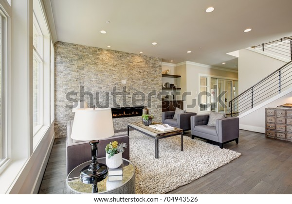 Moderna grande camera dispone di un pavimento a soffitto camino in pietra, grigio divano trapuntato abbinato a due poltrone grigie sopra soffice tappeto. Northwest, Stati Uniti d'America