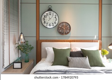 Modern green and brown bedroom with striped pattern. large wall clock on wall.