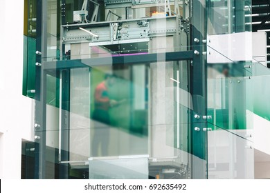 Modern green glass elevator for lifting people to the upper floors of high building ,office and shopping, mall and hotel.