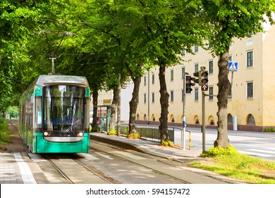 Modern green tram in Helsinki. City public high-tech electric vehicle in industrial European metropolis. Tram lines run along green alley, tram station Rautalammintie. Suomi, Helsinki, Finland