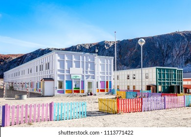 Modern greenlandic kindergarten with playground and colorful fence in tundra with rocky hills in the background, Kangerlussuaq, Greenland