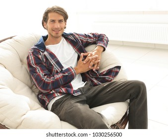 modern guy sitting in a large comfortable chair.