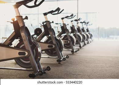 Modern gym interior with equipment. Row of training exercise bikes detail, backlight. Healthy lifestyle concept