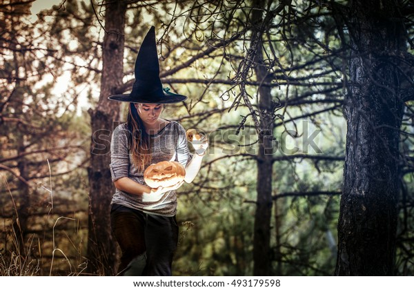 modern halloween witch in the forest with scary jack pumpkin in her hands