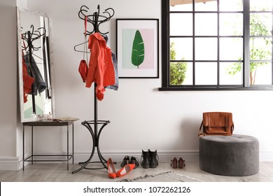 Modern hallway interior with clothes on hanger stand and mirror