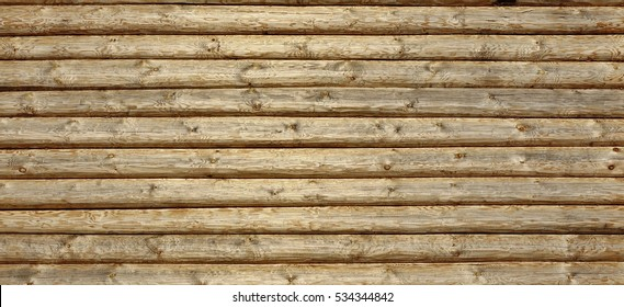 Modern Hand Hewn Natural Log Cabin Or Barn Wall Texture. Rustic Wooden House Horizontal Timbered Background. Unpainted Building Wood Facade. Abstract Banner.