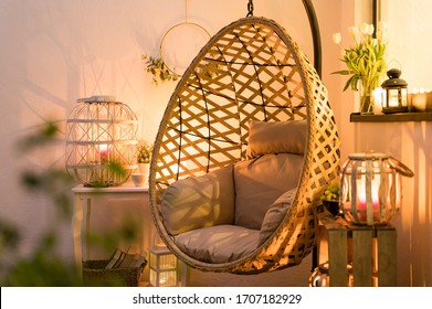 Modern hanging bamboo chair with a cosy beige pillow, candles, lanterns and flowers on a summer evening terrace