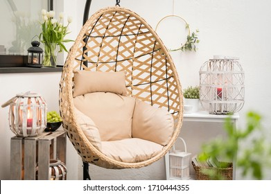 Modern hanging bamboo chair with a cosy beige pillow, candles, lanterns and flowers on a summer terrace with a white wall in the background