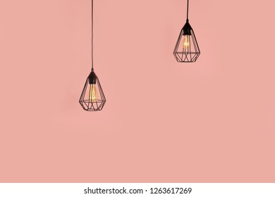 Modern hanging lamps on color background, space for text. Idea for interior design