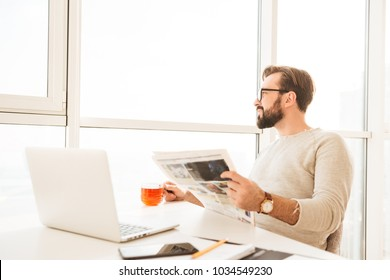 Modern happy guy 30s with beard and mustache looking at window when drinking tea and reading newspaper in his workplace at home