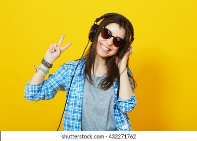 Modern happy millennial teenage girl with sunglasses, headphones smiling showing peace gesture over yellow background, vibrant colors.