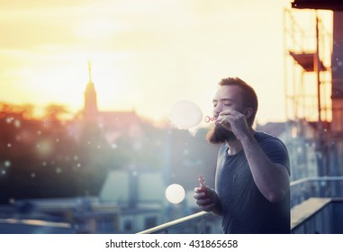 Modern happy young man with a beard fun Vaporizers, smoke and bubbles on the terrace. In the background, the evening sunset over the old city