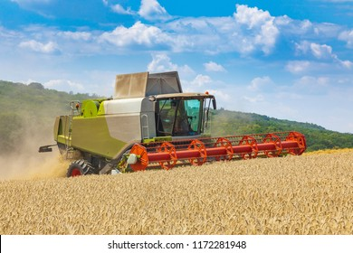 modern harvester during harvest of wheat on sunny day