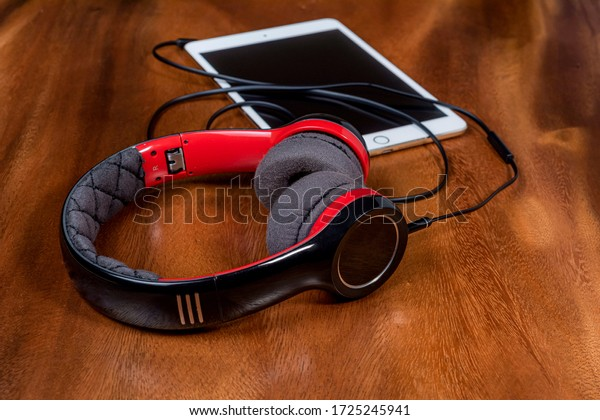 Modern headphone close up view with tablet on wooden table