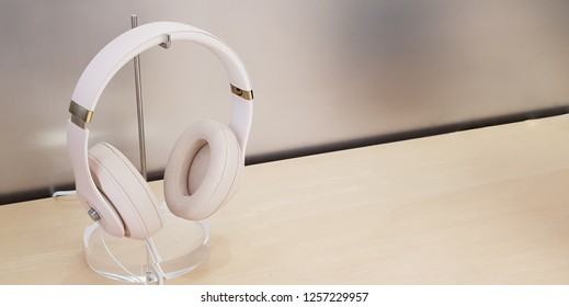 Modern headphones displayed on light wooden stand and background with room for text, isolated.