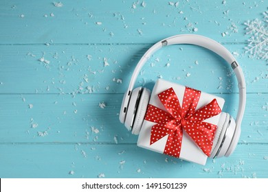 Modern headphones and gift box on blue wooden background, top view with space for text. Christmas music concept
