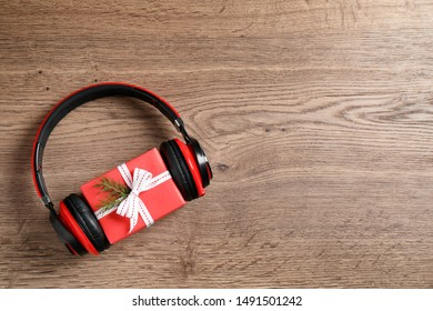 Modern headphones and gift box on wooden background, top view with space for text. Christmas music concept
