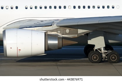 modern heavy widebody jet aircraft side detail including passenger windows with passengers silhouette, jet engine, nacelle, gear, slats extended close up view