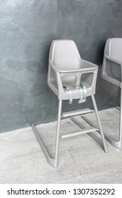 Modern high chair for baby feeding made of plastic with seat belts against dark concrete background.