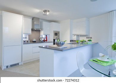 Modern high gloss finish kitchen incorporating built-in appliances, granite worktops and breakfast area with dressed table