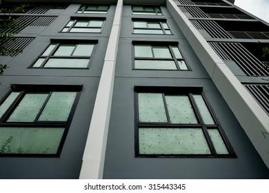A modern high rise condominium tower rising into a clear blue sky