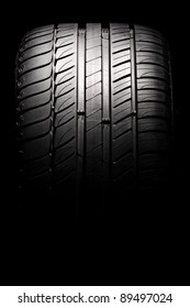 Modern high-performance sport summer tire isolated on a black background. Vertical composition.