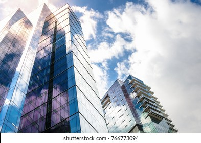 Modern High-rise Glass Buildings with Steel Frames Reflecting the Sky