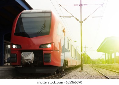 Modern high-speed train on a clear day with motion blur. Beautiful railway station with modern red commuter train.