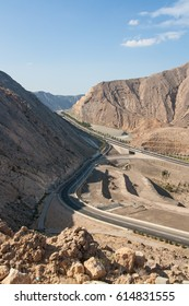 A modern highway cuts through the rugged cliffs of Wadi Kabir in the Sultanate of Oman, with Muscat visible in the distance