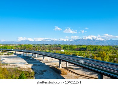 The Modern Highway in Piedmont on the Background of Snow-capped Alps, Italy