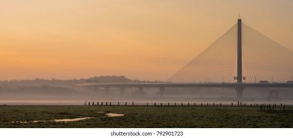 Modern highway road bridge in orange  foggy winter sunrise, Warrington, Cheshire, England
