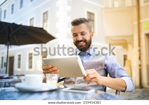 Modern hipster businessman drinking espresso coffee in the city cafe during lunch time and working on tablet