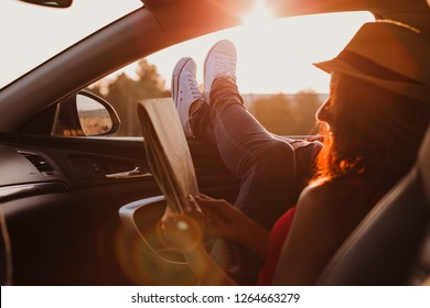 Modern hipster girl resting in a car and reading a map. Woman with feet on car door. Feet outside the window at sunset