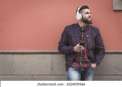 Modern hipster with red checkers shirt and blue jeans holding cellphone on street. Young stylish bearded man listening to music in the city. Leisure time alone. Millennial generation concept