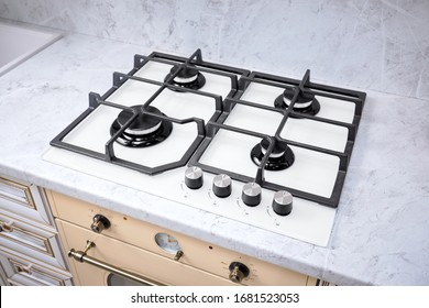 Modern hob gas stove made of tempered white glass using natural gas or propane for cooking products on light countertop in kitchen interior.