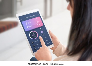 Modern home conrol app with flat desing user interface on tablet in woman hads. Home interior in background.