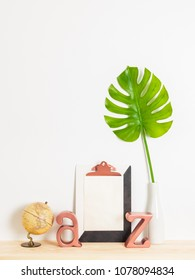 Modern home decor. Blank sheet of paper with copy space on a clipboard, green leaf, globe and metal letters on a wooden shelf.