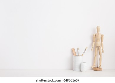Modern home decor mock up. Creative desk with wooden manequin, desk objects, office supplies, books and plant on a white background.