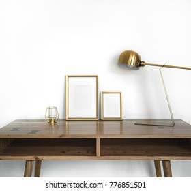 Modern home decor mock-up. Golden frames on wooden design table with gold metal lamp, candle against white wall. Background styled minimal interior mockup.