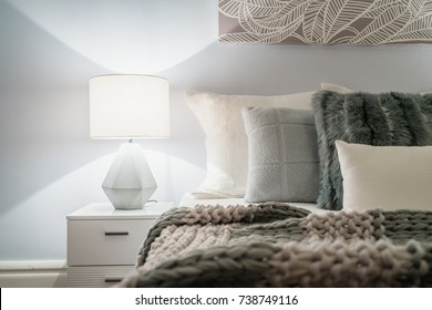 Modern home interior with bedroom setting including bedside table with lamp.