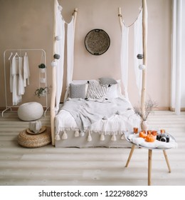 Modern home interior design. Bed with wooden canopy and pillows, blanket. Exotic bedroom interior, scandinavian style