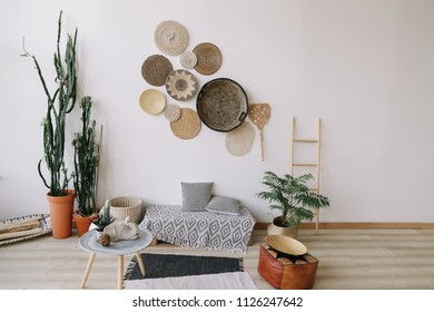 Modern home interior design. Boho style, exotic home interior design with decorative straw plates on the wall