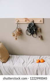Modern home interior design. Interior details of children's room on light background. Decorative wooden hanger with bag  on white wall. Exotic bedroom interior