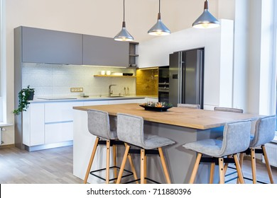 Modern home interior. Modern kitchen design in light interior. Kitchen island in room. Kitchen and living room combined. European furniture, design, technologies. Painted facades. Project management.