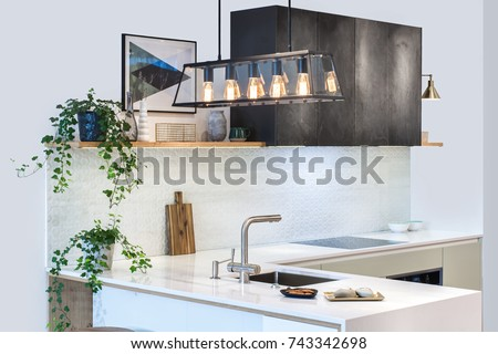 Modern home interior. Modern kitchen design in a light interior. Facades are painted and made of natural stone. European furniture, design, technologies. Pendant lights. Project management.