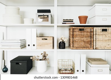 Modern home office cabinet interior design concept. White storage shelves rack with boxes, eucalyptus, decorations.