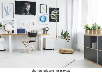 Modern home office with desk, chair, posters and big window