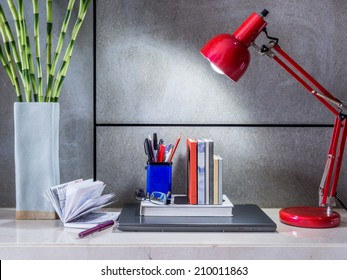 Modern home office desk with laptop, lamp and vase of flowers