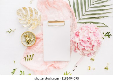 Modern home office desk workspace with blank paper clipboard, pink hydrangea flowers bouquet, tropical palm leaf, pastel blanket, monstera leaf plate and accessories on white background. Flatlay